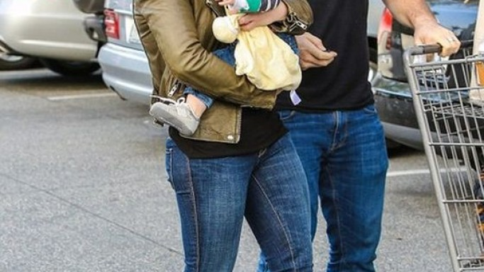 Wearing an olive leather, vintage wash biker jacket, Hilary Duff was seen carrying her little baby while walking alongside husband Mike Comrie.